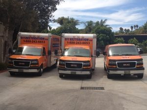 Water Damage Restoration Van And Trucks At Commercial Job Location